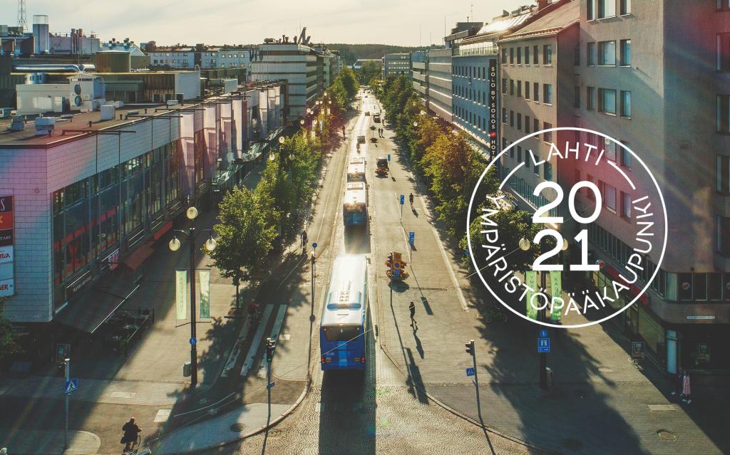Kesäinen ilmakuva busseista Aleksanterinkadulla ja kuvan päällä Lahti ympäristöpääkaupunki 2021 leima.