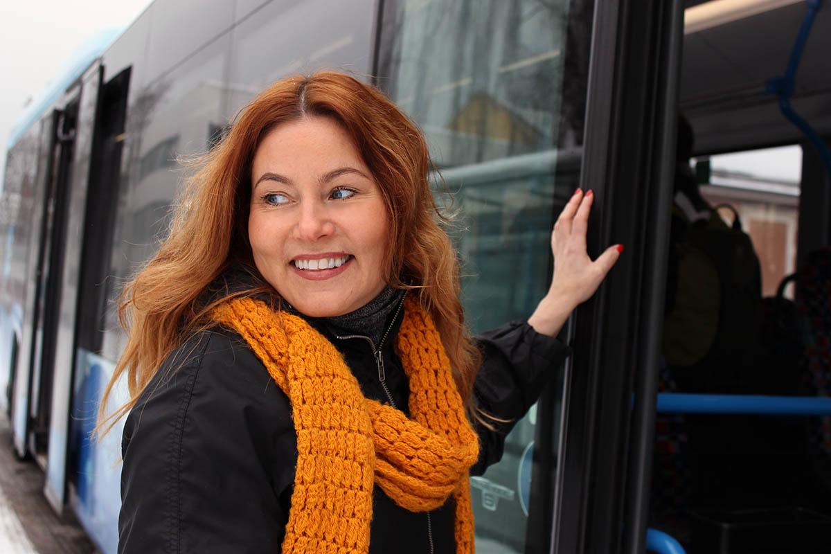 Hymyilevä nainen nousemassa bussiin.